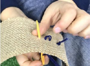 Plastic needle being sewn through burlap