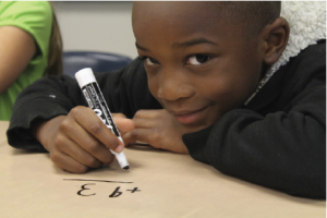 A smiling child doing math