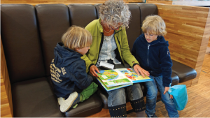 Two children being read a book by an adult